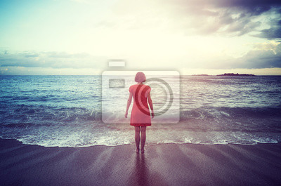 Woman standing on a beach facing the horizon at sunset, color toning applied.