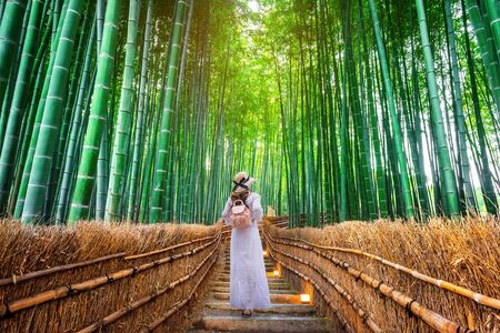 Obraz Woman walking at Bamboo Forest in Kyoto, Japan.