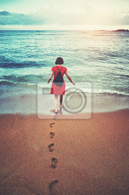 Woman walks toward the sea at sunset, color toned picture.