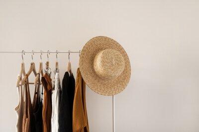 Obraz Women's fashion bright pastel clothes on clothing rack on white background. Minimalist fashion blog concept.