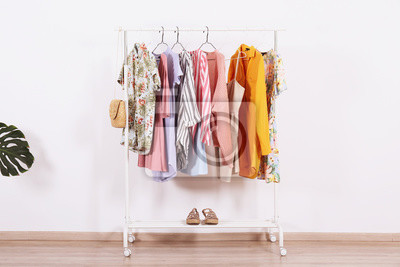 Obraz Women's hip clothing store interior concept. Row of different colorful female clothes hanging on rack in hipster fashion show room in shopping mall. White wall background. Copy space.