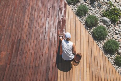 Obraz Wood deck renovation treatment, the person applying protective wood stain with a brush, overhead view of ipe hardwood decking restoration process