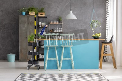 Wooden bar stools and blue dining table under lamp in room interior with grey wall, metal locker and bin