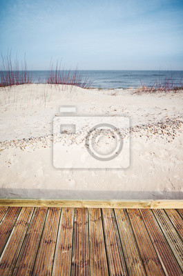 Wooden boardwalk by a beach, color toned picture.