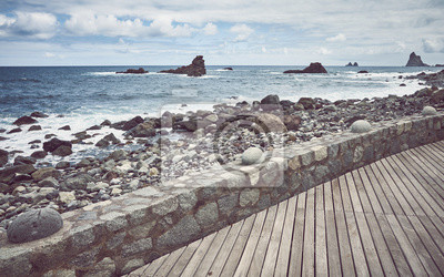 Wooden boardwalk by the Roque de Las Bodegas Beach, retro color toning applied, Tenerife, Spain.