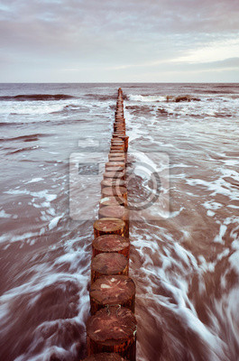 Wooden breakwater at sunrise, long exposure picture, living coral color toning applied.