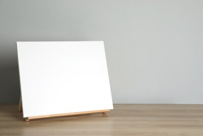 Obraz Wooden easel with blank canvas on table. Space for text