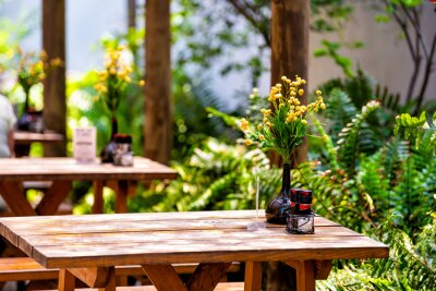 Obraz Wooden outside outdoor sitting restaurant empty area with picnic wooden tables chairs bench in patio terrace garden with green plants in Florida with flower bouquet and condiments