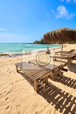 Wooden sunbeds on a tropical beach.