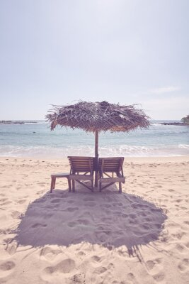 Wooden sunbeds under palm leaf umbrella on a tropical beach, color toning applied.
