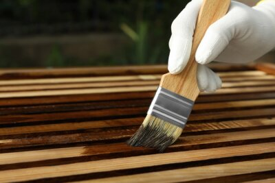 Obraz Worker applying wood stain onto planks outdoors, closeup