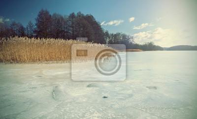 Wyblakłe i stylu retro obraz zamarzniętym jeziorze.
