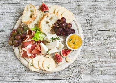 Obraz wyśmienitą przystawkę do wina - szynka, ser, winogrona, krakersy, figi, orzechy, dżem, podawane na lekkim drewnianym pokładzie