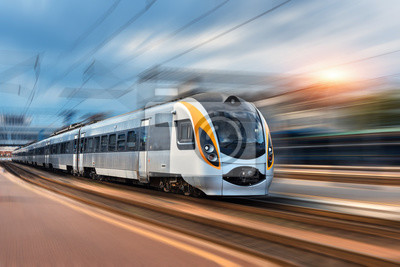 Wysoka prędkość pociągu w ruchu na dworcu o zachodzie słońca w Europie. Nowoczesny pociąg intercity na platformie kolejowej z efektem rozmycia ruchu. Krajobraz przemysłowy z pociągiem pasażerskim na t