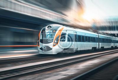 Wysoka prędkość pociągu w ruchu na stacji kolejowej o zachodzie słońca w Europie. Nowoczesny pociąg intercity na platformie kolejowej z efektem rozmycia ruchu. Krajobraz przemysłowy z pociągiem pasaże