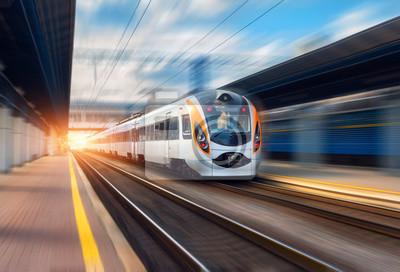Wysoka prędkość pociągu w ruchu na stacji kolejowej o zachodzie słońca w Europie. Nowoczesny pociąg intercity na platformie kolejowej z efektem rozmycia ruchu. Scena przemysłowa z poruszającym się poc