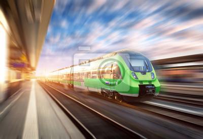 Wysoka prędkość pociągu w ruchu na stacji kolejowej o zachodzie słońca w Europie. Piękny zielony nowoczesny pociąg na platformie kolejowej z efektem rozmycia ruchu. Scena przemysłowa z pociągiem pasaż