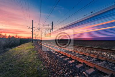 Wysoki prędkość pociąg pasażerski w ruchu na linii kolejowej przy zmierzchem. Zatarcie nowoczesnej pociągiem podmiejskim. Stacja kolejowa i kolorowy niebo. Podróże koleją, turystyka kolejowa. Krajobra