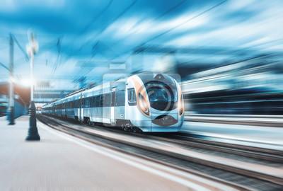 Wysoki prędkość pociąg pasażerski w ruchu na staci kolejowej przy zmierzchem w Europa. Nowoczesny pociąg intercity na peronie kolejowym z efektem rozmycia w ruchu. Miejska scena z linii kolejowej. Tra