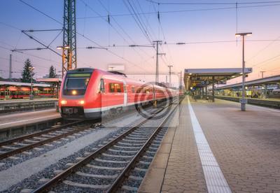 Wysokiej prędkości czerwony pociąg na stacji kolejowej o zachodzie słońca. Norymberga, Niemcy. Kolorowy krajobraz miejski. Nowoczesny pociąg intercity na peronie kolejowym w nocy. Dojeżdżający pociąg