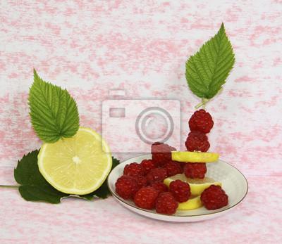 Obraz Малина с лимоном на блюдце на розовом фоне