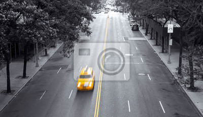 Yellow taxi speeding down 42nd Street through a black and white Midtown Manhattan cityscape in New York City