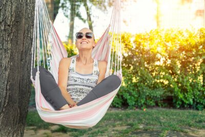 Obraz Young adult happy short haired shaved bald attractive woman chilling enjoy relaxing sitting in fabric chair hammock at yard in garen near house. Peaceful and idyllic outdoor rest lifestyle
