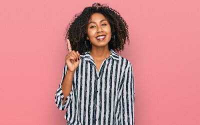 Obraz Young african american girl wearing casual clothes showing and pointing up with finger number one while smiling confident and happy.