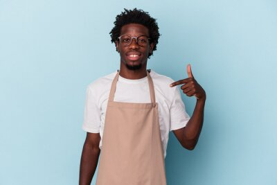 Obraz Young african american store clerk isolated on blue background person pointing by hand to a shirt copy space, proud and confident