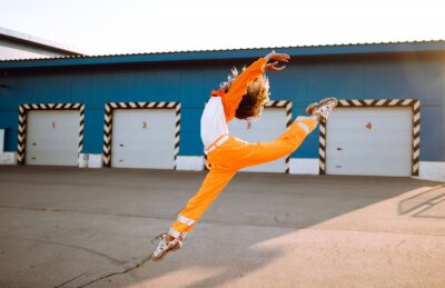 Obraz Young African American woman - dancer dancing in the street at sunset. Stylish woman with curly hair in an orange suit  showing some moves. Sport, dancing and urban culture concept.