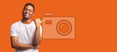 Obraz Young afro guy pointing at copy space with thumb up