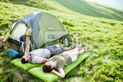 Obraz Young and cheerful couple lying on the mattress at the campsite, enjoying summer time while traveling in the mountains