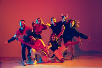Obraz Young and crazy. Stylish men and woman dancing hip-hop in bright clothes on green background at dance hall in neon light. Youth culture, movement, style and fashion, action. Fashionable portrait.