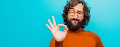Obraz young bearded crazy man feeling happy, relaxed and satisfied, showing approval with okay gesture, smiling against flat color wall
