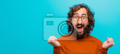 Obraz young bearded crazy man feeling shocked, excited and happy, laughing and celebrating success, saying wow! against flat color wall