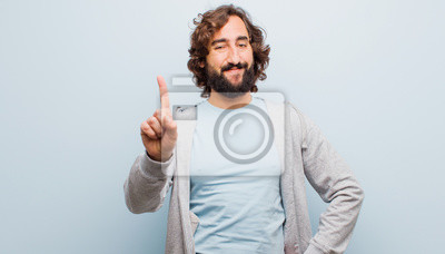 Obraz young bearded crazy man smiling and looking friendly, showing number one or first with hand forward, counting down against flat color wall
