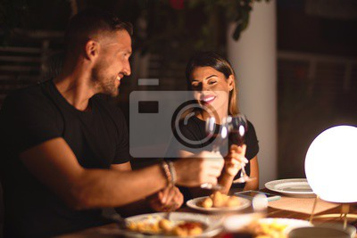 Obraz Young beautiful couple dinning on celebration toasting and smiling at terrace