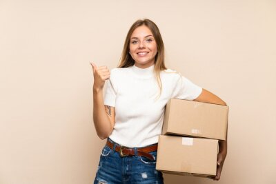 Obraz Young blonde woman over isolated background holding a box to move it to another site and pointing side