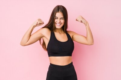 Obraz Young caucasian fitness woman doing sport isolated showing strength gesture with arms, symbol of feminine power