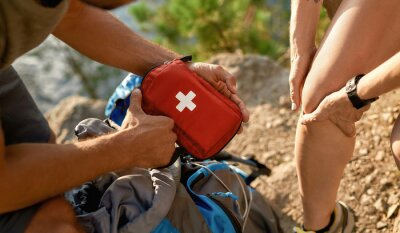 Obraz Young caucasian man holding first aid kit for healing