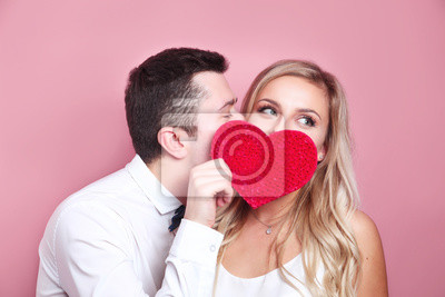 Obraz Young couple holding red love heart over eyes and kissing