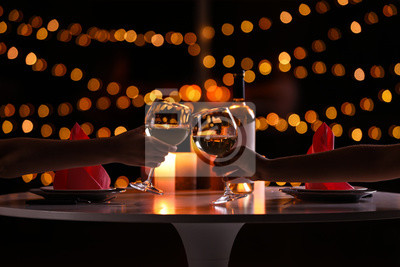 Obraz Young couple with glasses of wine having romantic candlelight dinner at table, closeup