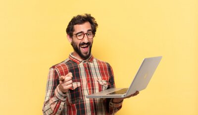 Obraz young crazy bearded man pointing or showing and a laptop