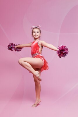 Obraz Young gymnast cheerleader girl doing an exercise on pink background. childrens professional sports. Cheerleading