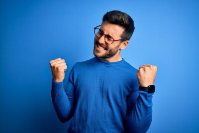 Obraz Young handsome man with beard wearing casual sweater and glasses over blue background very happy and excited doing winner gesture with arms raised, smiling and screaming for success. Celebration