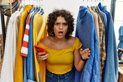 Obraz Young hispanic woman searching clothes on clothing rack using smartphone in shock face, looking skeptical and sarcastic, surprised with open mouth