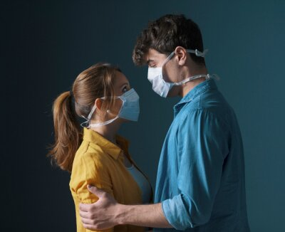 Obraz Young loving couple wearing face masks