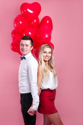 Obraz young loving couple with balloons heart on pink background