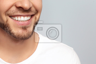 Obraz Young man with beautiful smile on grey background. Teeth whitening