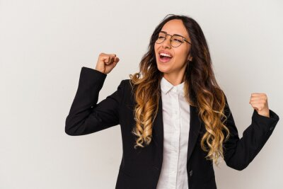 Obraz Young mexican business woman isolated on white background raising fist after a victory, winner concept.